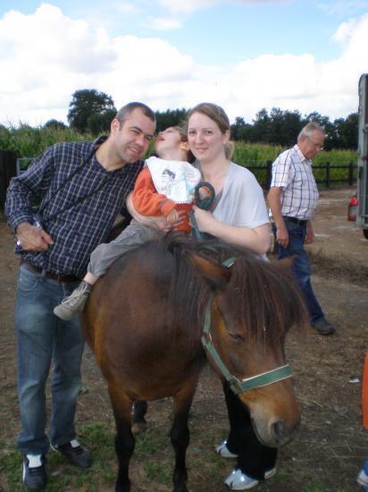 Dylan sur le poney entouré de papa et maman.